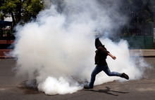 A masked student from the public university U.S.A.C. kicks away a tear gas canister fired by riot police during a protest in Guatemala City, Wednesday, June 6, 2012. Education students are protesting a reform by the Education Ministry that would add years of study for students specializing in certain areas. (AP Photo/Rodrigo Abd)