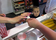 FILE- In this April 17, 2012 file photo, Gavin Rivera watches his mother purchase ice cream in Belmar N.J.  Americans cut back sharply on their credit card purchases in April, a sign that some may be worried about the slowdown in hiring. (AP Photo/Wayne Parry, File)
