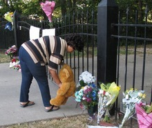 Neighbor Joann Williams leaves a large teddy bear at the fence around the home of Ron and Rebecca Bramlage, Thursday, June 7, 2012, in Junction City, Kan. The Bramlages died in a Florida plane crash. (AP Photo/John Hanna)