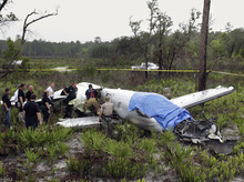 Emergency personnel investigate the site where a Pilatus PC-12, a single-engine turboprop passenger plane, crashed in southeast polk County near Lake Weohyakapka, aka Lake Walk In the Water, in southeast Polk County, Fla. on Thursday, June 7, 2012. Ronald Bramlage, 45, of Junction City, Kan., who was piloting the plane, his wife Rebecca and their four children were killed in the crash. (AP Photo/The Lakeland Ledger, Pierre DuCharme)  TAMPA TRIBUNE OUT