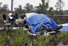Investigators work the site where a Pilatus PC-12, a single-engine turboprop passenger plane, crashed in southeast polk County near Lake Weohyakapka, aka Lake Walk In the Water, in southeast Polk County, Fla. on Thursday, June 7, 2012. Ronald Bramlage, 45, of Junction City, Kan., who was piloting the plane, his wife Rebecca and their four children were killed in the crash. (AP Photo/The Lakeland Ledger, Pierre DuCharme)  TAMPA TRIBUNE OUT