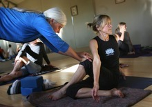 Kim Raff | The Salt Lake Tribune Charlotte Bell helps Sandy MacLeod with a pose while leading a yoga class recently in Salt Lake City. Bell recently published a book called
