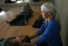 Kim Raff | The Salt Lake Tribune Charlotte Bell helps Charlyn Raaberg into a position while leading a yoga class at the IWKI studio in Salt Lake City on May 30, 2012. Bell recently published a book called