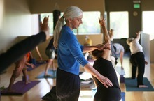 Kim Raff | The Salt Lake Tribune Charlotte Bell helps Sandy MacLeod with a pose while leading a yoga class at the IWKI studio in Salt Lake City on May 30, 2012. Bell recently published a book called