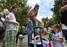 Scott Sommerdorf  |  The Salt Lake Tribune              Two young girls get balloon animals from a balloon artist on stilts at the opening Saturday of the Salt Lake Farmers Market, Saturday, June 9, 2012.