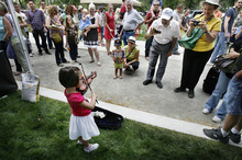 Scott Sommerdorf  |  The Salt Lake Tribune              Three-year-old Samantha Ricks playing a tiny violin captivates the passersby at the opening Saturday of the Salt Lake Farmers Market, Saturday, June 9, 2012.