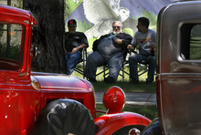 Scott Sommerdorf  |  The Salt Lake Tribune              Friends Dave Bernini, left, Larry Neilsen, and his son Ross, right, lounge near the Tracy Aviary on the south side of Liberty Park as they show their classic cars, Sunday, June 10, 2012. Larry Neilsen's red customized 1934 Ford pickup is at left.
