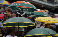 Spectators leave center court as rain delays the final opposing Spain's Rafael Nadal and Serbia's Novak Djokovic in the French Open tennis tournament at the Roland Garros stadium in Paris, Sunday, June 10, 2012.   (AP Photo/Christophe Ena)