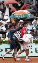 Spain's Rafael Nadal leaves the court as rain delays his match against Serbia's Novak Djokovic during their men's final in the French Open tennis tournament at the Roland Garros stadium in Paris, Sunday, June 10, 2012.  (AP Photo/Bernat Armangue)