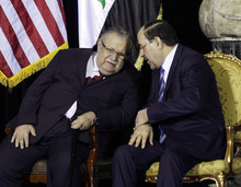 FILE - In this Dec. 1, 2011 file photo, Iraqi President Jalal Talabani, left, and Iraqi Prime Minister Nouri al-Maliki, chat during a special ceremony at Camp Victory in Baghdad. Opponents of Al-Maliki have failed to muster enough support to bring him down in a vote of no confidence, Talabani said in a statement posted on his website Sunday, June 10, 2012. (AP Photo/Khalid Mohammed, Pool, File)