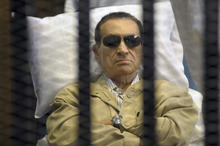 FILE - In this June 2, 2012 file photo, Egypt's ex-President Hosni Mubarak lies on a gurney inside a barred cage in the police academy courthouse in Cairo, Egypt, during a hearing in which he was sentenced to life in prison for his role in the killing of protesters during the revolution in spring of 2011. Mubarak's health sharply deteriorated Wednesday, June 7, 2012, and specialists were evaluating whether to transfer him to a better-equipped hospital outside the penal system, security officials said. (AP Photo/File)