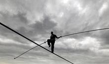 Nik Wallenda performs a walk on a tightrope in the rain during training for his walk over Niagara Falls in Niagara Falls, N.Y., Wednesday, May 16, 2012. (AP Photo/David Duprey)