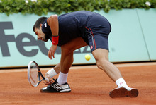 Serbia's Novak Djokovic misses a ball as he plays Spain's Rafael Nadal during their men's final match in the French Open tennis tournament at the Roland Garros stadium in Paris, Sunday, June 10, 2012.  (AP Photo/Michel Euler)