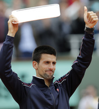 Novak Djokovic of Serbia holds the second place trophy after losing to Rafael Nadal of Spain at the French Open tennis tournament in Roland Garros stadium in Paris, Monday June 11, 2012. Rain suspended the final making it the first French Open not to end on Sunday since 1973. Nadal clinched his seventh title in four sets 6-4, 6-3, 2-6, 7-5, passing Sweden's Bjorn Borg as the all-time record-holder for French Open titles. (AP Photo/Christophe Ena)