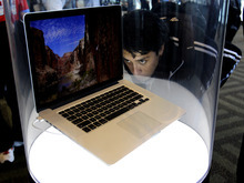 An attendee looks at the new MacBook Pro on display at the Apple Developers Conference in San Francisco, Monday, June 11, 2012. New iPhone and Mac software and updated Mac computers were among the highlights Monday at Apple Inc.'s annual conference for software developers. (AP Photo/Paul Sakuma)