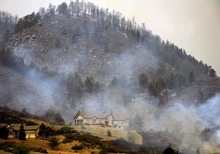A wildfire burns in a mountainous area about 15 miles west of Fort Collins, Colo., on Sunday, June 10, 2012. Firefighters on Sunday were fighting wildfires that have spread quickly in parched forests in Colorado and New Mexico, forcing hundreds of people from their homes and the evacuation of wolves from a sanctuary. The Colorado fire grew to 22 square miles within about a day of being reported and has destroyed or damaged 18 structures. (AP Photo/The Denver Post, Helen H. Richardson) MAGS OUT; TV OUT; INTERNET OUT; MANDATORY CREDIT