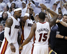 Miami Heat's Chris Bosh, center, Mario Chalmers, right, and LeBron James congratulate each other during the second half of Game 7 of the NBA basketball playoffs Eastern Conference finals against the Boston Celtics, Saturday, June 9, 2012, in Miami. The Heat defeated the Celtics 101-88. (AP Photo/Lynne Sladky)