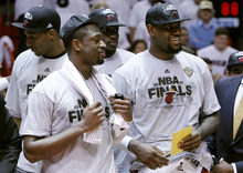 Miami Heat's LeBron James, right, receives an envelope as he stands with Dwyane Wade, left, during the trophy presentation following the Heat's 101-88 victory over the Boston Celtics in Game 7 in the NBA basketball playoffs Eastern Conference finals Saturday, June 9, 2012, in Miami. (AP Photo/Lynne Sladky)