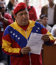 Venezuela's President Hugo Chavez shows a registration certificate as he poses for pictures at the headquarters of the National Elections Council, CNE,  in Caracas, Venezuela, Monday, June 11, 2012. Chavez rallied thousands of his supporters Monday, wearing his signature red beret and singing a folk song as he formalized his presidential candidacy and launched his re-election bid. (AP Photo/Fernando Llano)