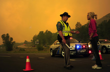 An official speaks with Brittany Harrington at a road closure near her home on Highway 287, due to a wildfire burning in a mountainous area about 15 miles west of Fort Collins, Colo., on Sunday, June 10, 2012. Firefighters on Sunday were fighting wildfires that have spread quickly in parched forests in Colorado and New Mexico, forcing hundreds of people from their homes and the evacuation of wolves from a sanctuary. The Colorado fire grew to 22 square miles within about a day of being reported and has destroyed or damaged 18 structures. (AP Photo/The Denver Post, AAron Ontiveroz) MAGS OUT; TV OUT; INTERNET OUT; MANDATORY CREDIT