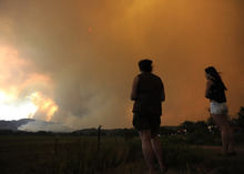Donna Dundon, left, and Arianna Roupinian, of Fort Collins, Colo., watch a fire burning in a mountainous area about 15 miles west of Fort Collins, on Sunday, June 10, 2012. Firefighters on Sunday were fighting wildfires that have spread quickly in parched forests in Colorado and New Mexico, forcing hundreds of people from their homes and the evacuation of wolves from a sanctuary. The Colorado fire grew to 22 square miles within about a day of being reported and has destroyed or damaged 18 structures. (AP Photo/The Denver Post, Helen H. Richardson) MAGS OUT; TV OUT; INTERNET OUT; MANDATORY CREDIT