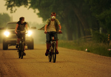 Caleb Armstrong and his mother, Cheryl, ride their bicycles near their home on County Road 56 through haze from a wildfire burning in a mountainous area about 15 miles west of Fort Collins, Colo., on Sunday, June 10, 2012. Firefighters on Sunday were fighting wildfires that have spread quickly in parched forests in Colorado and New Mexico, forcing hundreds of people from their homes and the evacuation of wolves from a sanctuary. The Colorado fire grew to 22 square miles within about a day of being reported and has destroyed or damaged 18 structures. (AP Photo/The Denver Post, AAron Ontiveroz) MAGS OUT; TV OUT; INTERNET OUT; MANDATORY CREDIT