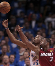 Oklahoma City Thunder small forward Kevin Durant (35) and Miami Heat shooting guard Dwyane Wade chase a loose ball during the second half at Game 1 of the NBA finals basketball series, Tuesday, June 12, 2012, in Oklahoma City. (AP Photo/Jeff Roberson)
