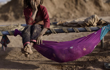 Pakistani Naginah Sadiq, 5, who works in a brick factory, rests on a bed next to her sister Shahzadi, 8 months, sleeping in a hammock attached to the bed, on World Day Against Child Labor, on the outskirts of Islamabad, Pakistan, Tuesday, June 12, 2012. The World Day Against Child Labor is observed on June 12 across the world including Pakistan to raise awareness and contribute to end child labor. Naginah earns 250 Rupees ($2 .77) per day according to her father. (AP Photo/Muhammed Muheisen)