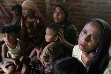 A Rohingya Muslim family who fled Myanmar to Bangladesh to escape religious violence sits at a shelter provided by local people in Taknaf, Bangladesh, Tuesday, June 12, 2012. Bangladesh on Tuesday turned away three boats carrying 1,000 Rohingya Muslims fleeing violence in neighboring Myanmar, bringing to 1,500 the number of refugees blocked in recent days, officials said. (AP Photo/Anurup Titu)
