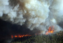 In this Saturday, June 9, 2012 photo, flames burn in the area near Larimer County Road 27 and Colorado Highway 14 of the High Park fire west of Fort Collins, Colo. (AP Photo/The Denver Post, Karl Gehring)  MAGS OUT; TV OUT; INTERNET OUT
