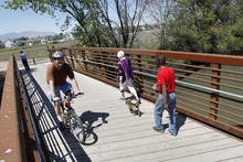 Al Hartmann     The Salt Lake Tribune  Bicyclists and walkers cross the Jordan RIver on a bridge at 1800 N. Redwood Road to access one of the last sections of the Jordan River Parkway Trail be be completed. The new section opened Thursday extends one mile and connects Salt Lake and Davis counties. The stretch includes a 10-foot-wide asphalt trail, 5-foot-wide horse trail and 1,000 feet of elevated boardwalk through a wetlands area.
