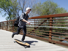 Al Hartmann     The Salt Lake Tribune  A skateborder crosses the Jordan RIver on a bridge at 1800 North Redwood Road to access one of the last sections of the Jordan River Parkway Trail to be completed .