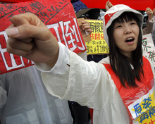 A demonstrator raises clenched fist during a rally, protesting against restarting the Ohi nuclear power plant's reactors in front of the prime minister's official residence in Tokyo, Saturday, June 16, 2012. Japan moved closer to restarting the nuclear reactors for the first time since last year's earthquake and tsunami led to a nationwide shutdown. A slogan worn by the protester reads: