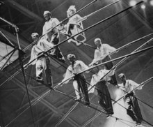 FILE- In this Jan. 30, 1962 file photo,  the Great Wallendas walk the high wire during their three-tier seven-person pyramid performance at the State Fair Coliseum in Detroit, Michigan. During the performance the pyramid formation collapsed and the performers fell to the ground injuring performers Jana Schepp and Mario Wallenda, as well as killing performers Richard Faughnan and Dieter Schepp.  From left to right, bottom row, are, Dieter Schepp; Mario Wallenda; Richard Faughnan and Gunther Wallenda.  From left ro right in the second row are Karl Wallenda and Herman Wallenda.  Sitting on chair is Jana Schepp. On Friday, June 15, 2012, Karl's great grandson, Nick Wallenda, will attempt a high wire walk over Niagara Falls on live television, hoping to write his famous family's name into the 153-year-old legend of daredevils who've