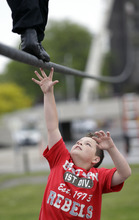 Nik Wallenda's son Amadaos reaches up to touch his father's feet as he performs a walk on a tightrope during training for his walk over Niagara Falls in Niagara Falls, N.Y., Wednesday, May 16, 2012. (AP Photo/David Duprey)