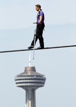 Nik Wallenda performs a walk on a tightrope with the Skylon Tower in the background during training in Niagara Falls, N.Y., Tuesday, May 22, 2012. Wallenda can't visit a new place without envisioning a wire strung high above his head: Linking buildings, landmarks, nations. Even as a 6-year-old at Niagara Falls with his parents, he pictured walking a tightrope over the raging, whitewater maw. Now 33, he's ready to live out that childhood fantasy when he attempts Friday, June 15, 2012 to become the first person ever to walk a tightrope directly over the brink of Niagara Falls. (AP Photo/David Duprey)