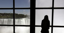 A tourist looks at Niagara Falls in Niagara Falls, Canada, Wednesday, June 13, 2012. On Friday night Nik Wallenda's attempt at being the first person to walk across the falls on a tightrope will be broadcast on a live ABC special, with CTV carrying it in Canada. (AP Photo/David Duprey)