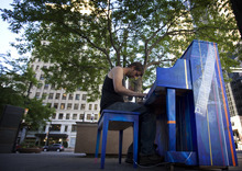Kim Raff | The Salt Lake Tribune Christopher Goudge plays a piano installed at Jones Waldo downtown as part of Utah Museum of Contemporary Art's