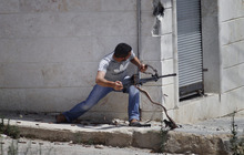 A Free Syrian Army fighter fires his weapon during clashes with Syrian troops near Idlib, Syria. (AP Photo)