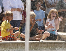 Leah Hogsten  |  The Salt Lake Tribune l-r Troupe Wagstaff, 3, brother Finn Wagstaff, 7, and their cousin Elesa Wiser, 7, enjoy getting sprayed by the fountain during the dedication Friday, June 15, 2012 in Farmington.  The Station Park shopping center in Farmington unveiled a world-class show fountain with choreographed lights, music, color and 30-60-foot high dancing water.