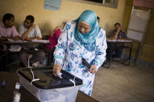 An Egyptian woman casts her vote at a polling station during the second day of the presidential runoff election in Alexandria, Egypt, Sunday, June 17, 2012. Egyptians are choosing between a conservative Islamist and Hosni Mubarak's ex-prime minister in a second day of a presidential runoff that has been overshadowed by the domination of the country's military. (AP Photo/Manu Brabo)