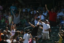 Kim Raff | The Salt Lake Tribune Fans catch a ball thrown into the stands during a Salt Lake Bees game against the Fresno Grizzlies at Spring Mobile Ballpark in Salt Lake City on June 17, 2012.