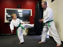 Kim Raff | The Salt Lake Tribune Dov Siporin holds the bag for his son, Matan, while warming up for his  lesson at Salt Lake Valley Tae Kwon Do Academy in Salt Lake City.