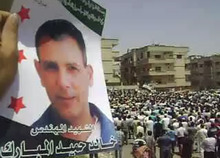 This image made from amateur video released by Shaam News Network and accessed Friday, June 15, 2012, purports to show protesters in Homs, Syria, including one holding a poster depicting a fallen activist Khalid Hameed al-Mubarak, whose na,e is written on the poster in Arabic. (AP Photo/Shaam News Network via AP video)THE ASSOCIATED PRESS CANNOT INDEPENDENTLY VERIFY THE CONTENT, DATE, LOCATION OR AUTHENTICITY OF THIS MATERIAL