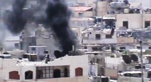 This image made from amateur video released by the Shaam News Network and accessed Saturday, June 16, 2012, purports to show black smoke leaping the air from a building in Joret el-Shayah, Homs, Syria. The Syrian government, intent on wresting back control of rebel-held areas, launched a fierce offensive in recent days to recover territories in several locations, shelling heavily populated districts and using attack helicopters over towns and cities. (AP Photo/Shaam News Network via AP video) TV OUT, THE ASSOCIATED PRESS CANNOT INDEPENDENTLY VERIFY THE CONTENT, DATE, LOCATION OR AUTHENTICITY OF THIS MATERIAL
