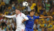 England's Wayne Rooney, left, and Ukraine's Yevhen Khacheridi go for a header during the Euro 2012 soccer championship Group D match between England and Ukraine in Donetsk, Ukraine, Tuesday, June 19, 2012. (AP Photo/Matthias Schrader)
