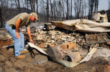 Mark Stambaugh, owner of Angus Firewood surveys the charred debris left after his business fell victim to the Little Bear fire near Ruidoso, N.M., on Monday, June 11, 2012. (AP Photo/Albuquerque Journal, Adolphe Pierre-Louis)