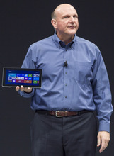 Microsoft CEO Steve Ballmer unveils the Surface, a tablet computer aiming compete with Apple's iPad at Hollywood's Milk Studios in Los Angeles Monday, June 18, 2012. The 9.3-millimeter thick tablet comes with a kickstand to hold it upright and keyboard that is part of the device's cover.  (AP Photo/Damian Dovarganes)