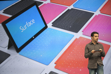 Panos Panay, the general manager of the Microsoft Surface holds up a Surface, the company's new tablet computer, at Hollywood's Milk Studios in Los Angeles Monday, June 18, 2012. The 9.3-millimeter thick tablet comes with a kickstand to hold it upright and keyboard that is part of the device's cover. (AP Photo/Damian Dovarganes)
