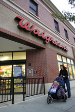 FILE -- In a Sept. 27, 2010 file photo shows a woman pushing a baby carriage past the entrance of a Walgreens pharmacy in Brookline, Mass.   Drugstore chain Walgreen Co. says it will spend $6.7 billion to buy a stake in health and beauty retailer Alliance Boots.   (AP Photo/Steven Senne, file)